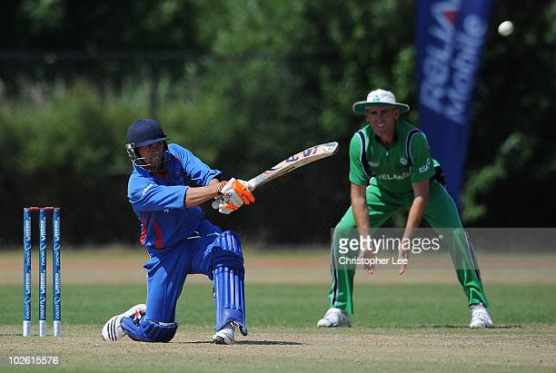 Shabir Noori of Afghanistan in action as Trent Johnson of Ireland watches during the ICC World Cricket League Division One match between Ireland and...