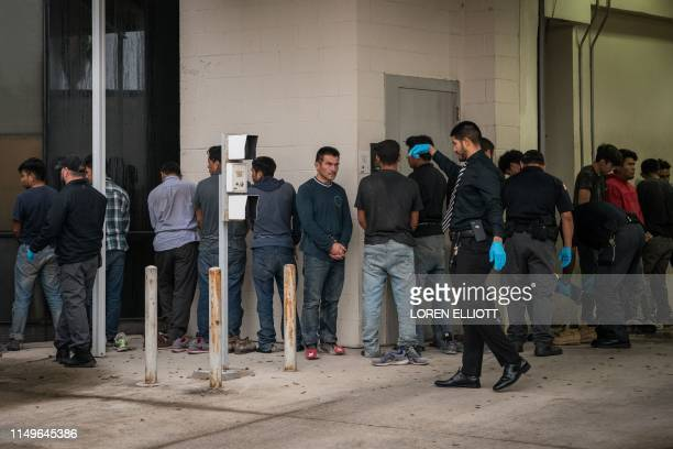Shackled migrants in federal custody are searched upon arriving for immigration hearings at the US federal courthouse on June 12 in McAllen, Texas.