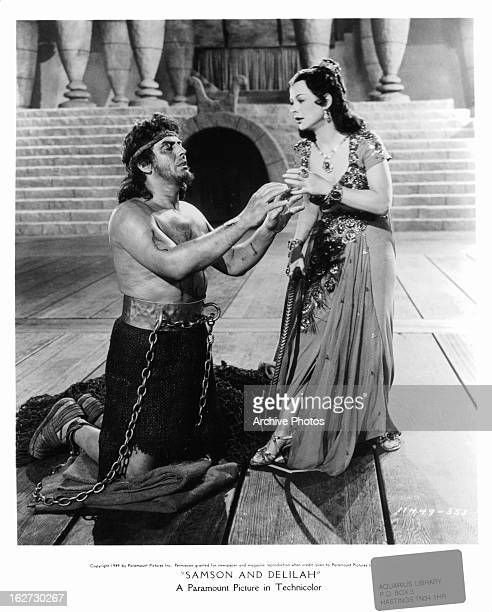 A shackled Victor Mature reaches up towards Hedy Lamarr in a scene from the film 'Samson And Delilah' 1949