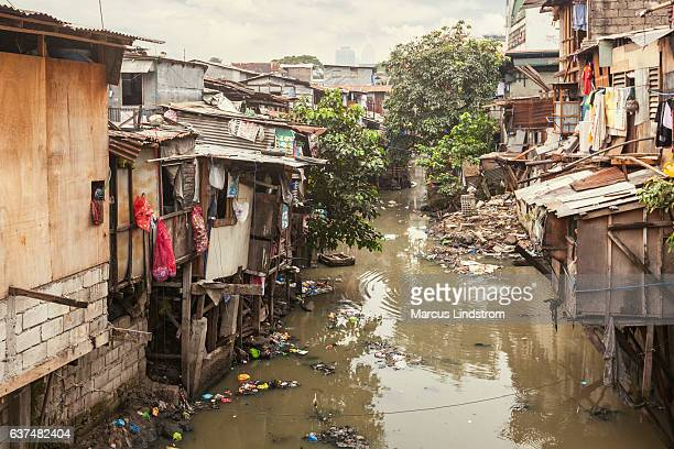shacks along a polluted canal - armoede stockfoto's en -beelden