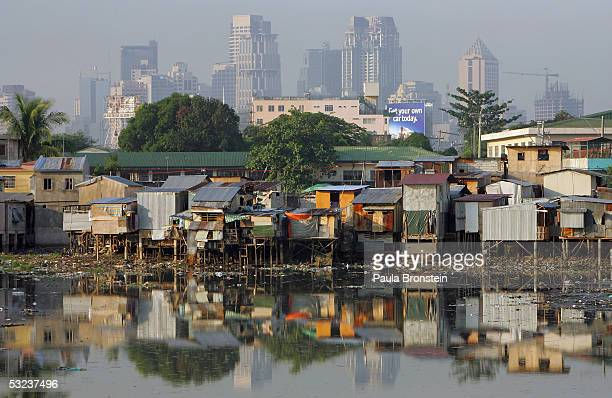Shacks stacked on top of each other stand out from the financial district of Makati skyline along the polluted Maricaban River in the slums on July...