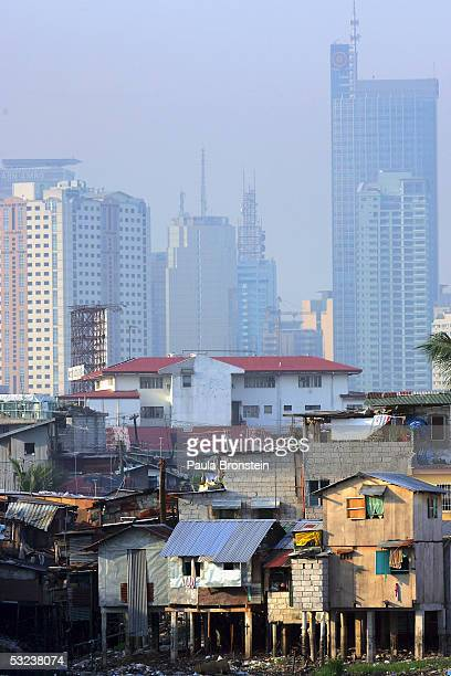 Shacks stacked on top of each other stand out from the financial district of Makati skyline along the polluted Maricaban River in the slums on July 9...