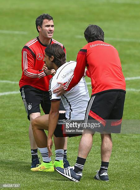 Shad Forsythe assistant coach gives Sami Khedira a helping hand during the German National team training session at StMartin training ground on May...