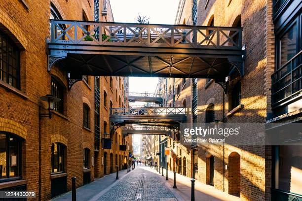 shad thames street lit with sunlight at sunset, london, uk - building exterior stock pictures, royalty-free photos & images