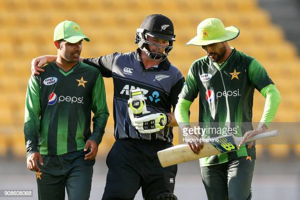 Shadab Khan and Mohammad Amir of Pakistan leave the field with Colin Munro of New Zealandat the end of play during game one of the Twenty20 series...