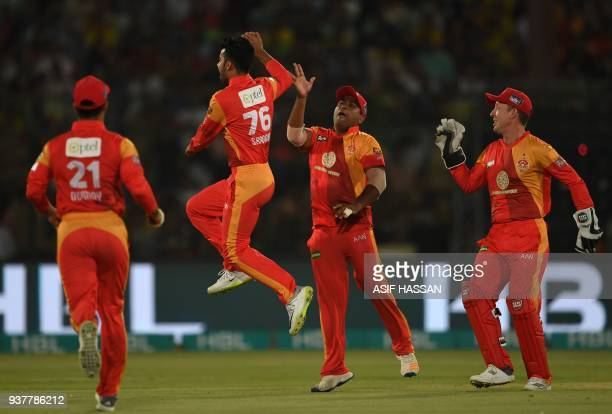 Shadab Khan of Islamabad United celebrates with teammates after taking the wicket of Darren Sammy of Peshawar Zalmi during the Pakistan Super League...