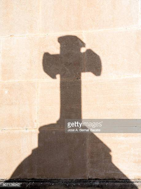 shade of an ancient cross on a wall of stone in a cemetery - empty tomb stock pictures, royalty-free photos & images