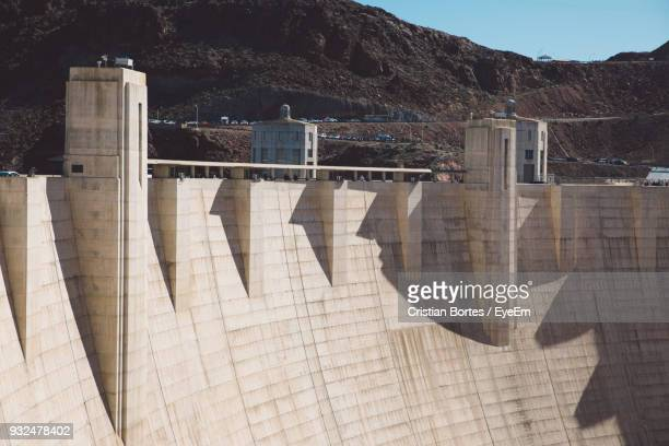 shadow against mountain during sunny day - hoover dam stock photos and pictures