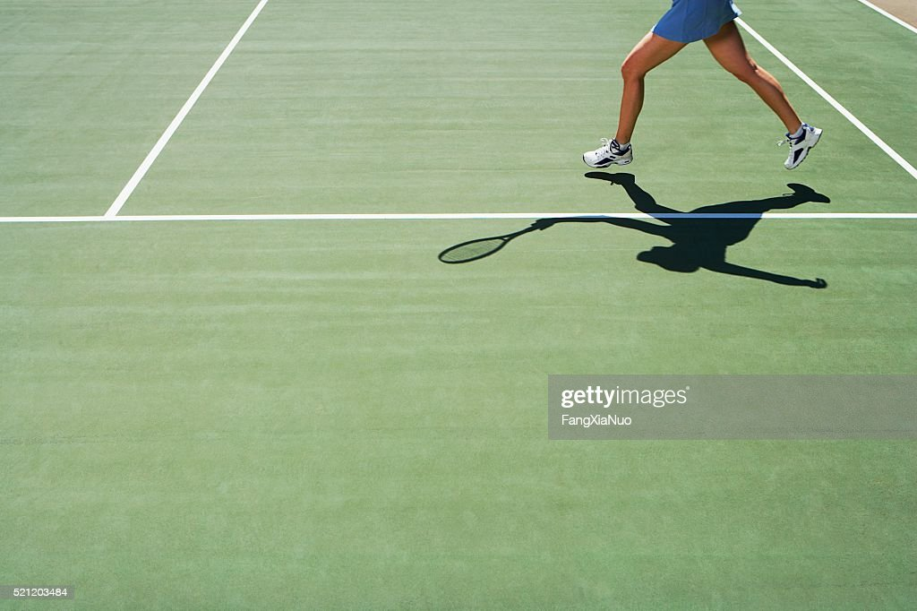Shadow and legs of person playing tennis : Photo