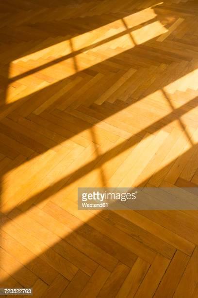 shadow and light on herringbone parquet flooring - herringbone floor stock photos and pictures