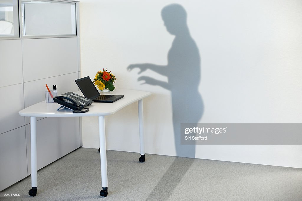 shadow attempting to use office equipment : Stock Photo
