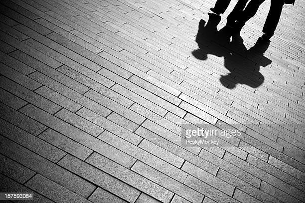 Shadow Businessmen Walk on Gray Paving Stones