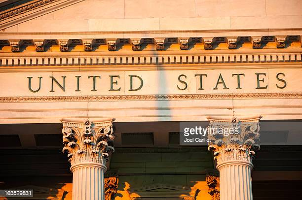 Shadow cast between United States on government building at sunset