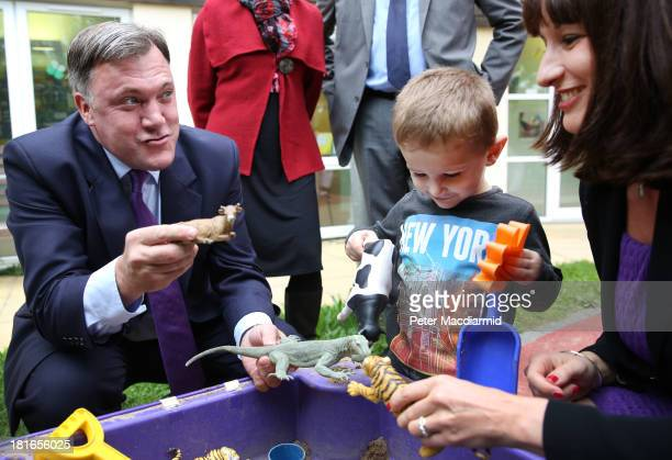 Shadow Chancellor Ed Balls pulls a face as he plays with three year old Connor Felton as Rachel Reeve MP looks on at the Roundabout Children's Centre...
