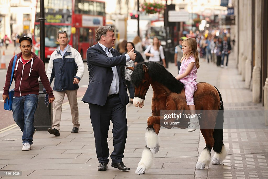 Shadow Chancellor of the Exchequer Ed Balls (C) chats to Lottie, aged 5, riding a Clydesdale Prancing Pony outside Hamleys toy shop on June 27, 2013 in London, England. Mr Balls happened to walk past as Hamleys were showcasing their predictions for the top selling toys for Christmas 2013.