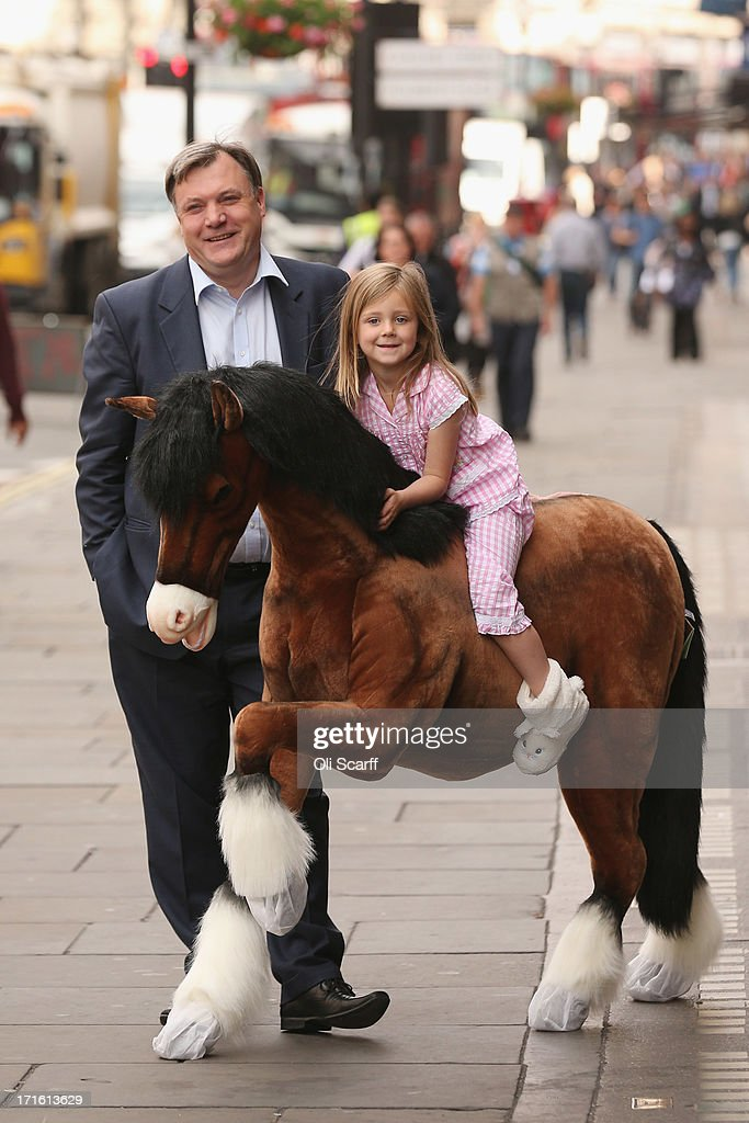 Shadow Chancellor of the Exchequer Ed Balls chats to Lottie, aged 5, riding a Clydesdale Prancing Pony outside Hamleys toy shop on June 27, 2013 in London, England. Mr Balls happened to walk past as Hamleys were showcasing their predictions for the top selling toys for Christmas 2013.