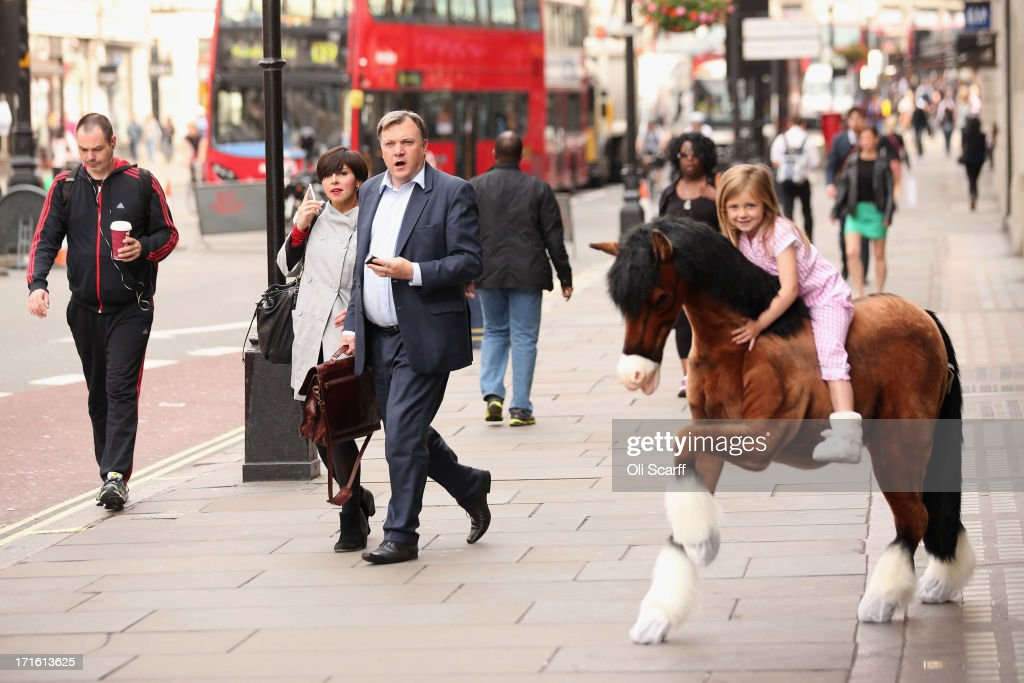 Shadow Chancellor of the Exchequer Ed Balls (C) looks shocked as he sees a group of press photographers taking pictures of Lottie, aged 5, riding a Clydesdale Prancing Pony outside Hamleys toy shop on June 27, 2013 in London, England. Mr Balls happened to walk past as Hamleys were showcasing their predictions for the top selling toys for Christmas 2013.