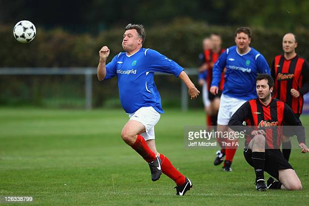 Shadow Chancellor of the Exchequer Ed Balls wins the ball ahead of journalist Graeme Demianyk during the Labour MP's v Press Lobby Party Conference...