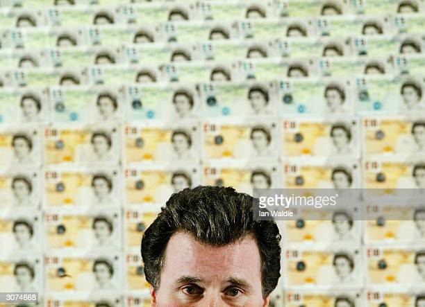 Shadow Chancellor Oliver Letwin holds a press conference in front of 5000 GBP in 5 and 10 bank notes March 11 2004 in London The cash represents what...