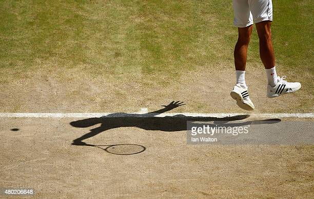 Shadow detail as Novak Djokovic of Serbia serves in the Gentlemens Singles Semi Final match against Richard Gasquet of France during day eleven of...