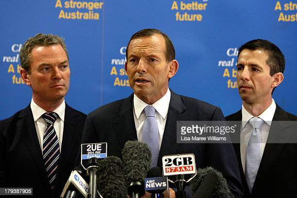 Shadow Education minister Christopher Pyne and Simon Birmingham MP look at Australian Opposition Leader Tony Abbott as he speaks to workers and the...