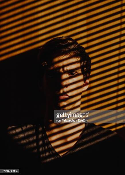 shadow falling on young man at home - jalousie stock-fotos und bilder