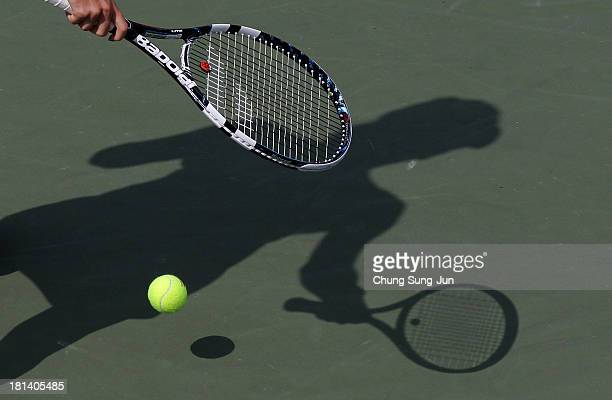 A shadow is cast across the court as Agnieszka Radwanska of Poland serves during her match against Lara Arruabarrena of Spain during day six of the...