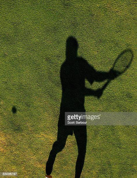 A shadow is cast as a player hits the ball during the completion of the second round match at the Stella Artois Tennis Championships at the Queen's...