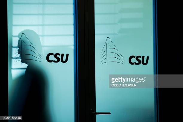 A shadow is seen on a glass door as the Christian Social Union leadership meet at their headquarters in Munich southern Germany on October 15 2018
