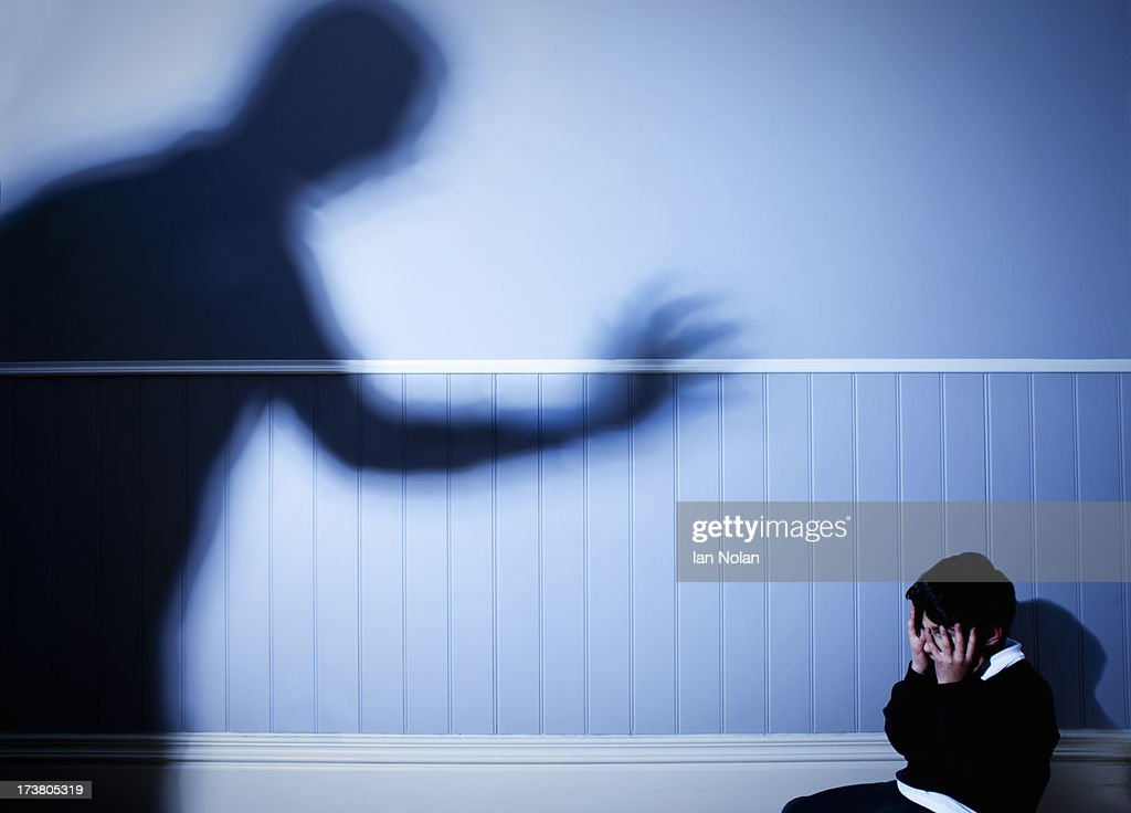 Shadow looming over frightened boy : Stockfoto