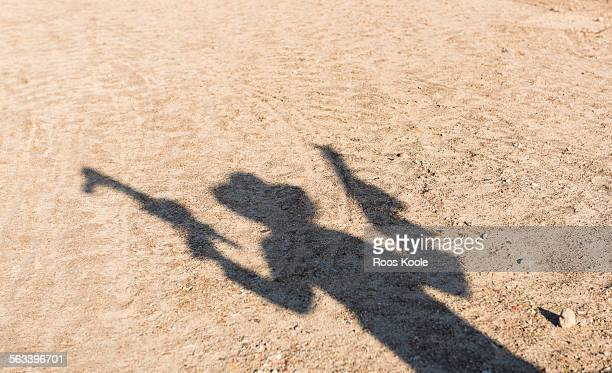 Shadow of a boy with toy guns