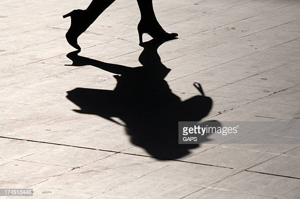 Shadow of a businesswoman in heels walking