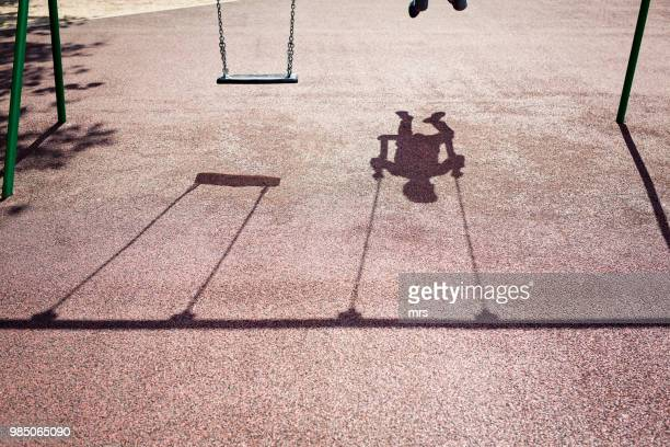 shadow of a child on a playground swing - schaduw stockfoto's en -beelden