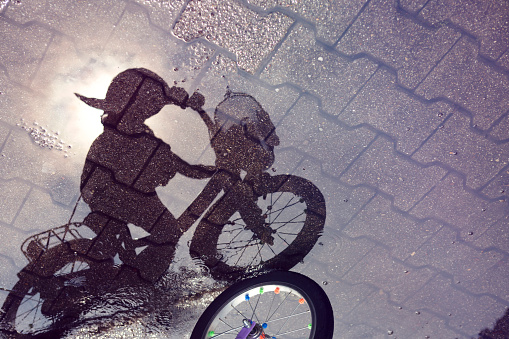 Shadow of a child riding a bicycle through a puddle - gettyimageskorea