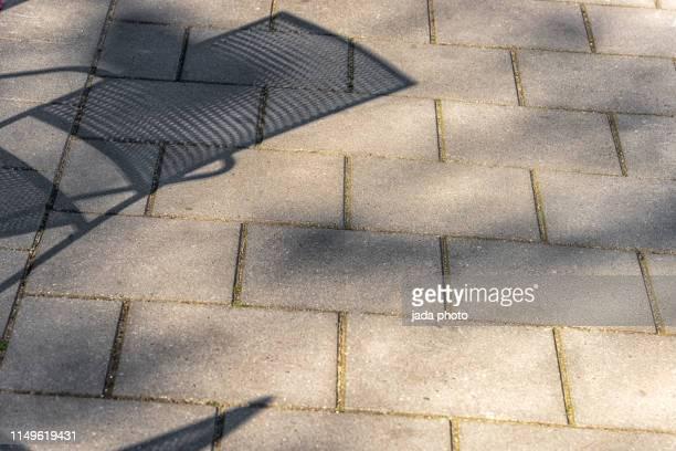 shadow of a garden chair spread over the tiles of a side-walk - stoep stockfoto's en -beelden