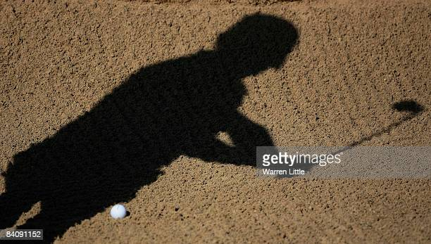 A shadow of a golfer is captured playing his bunker shot during the second round of the South African Open Championship at Pearl Valley Golf Country...