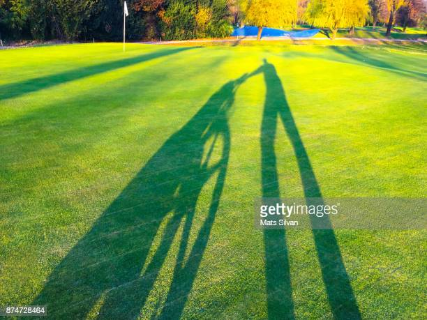 shadow of a golfer pulling golf bag - ascona stock photos and pictures
