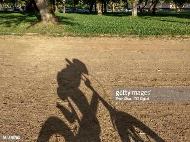 Shadow of a kid playing bike