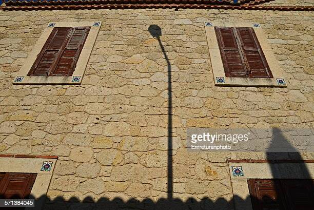 shadow of a lamp post on a stone wall - emreturanphoto stock pictures, royalty-free photos & images