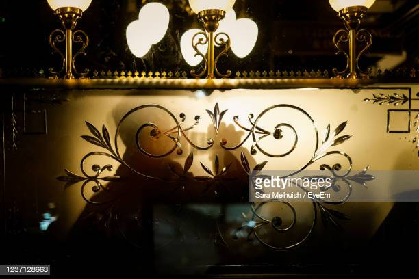 a shadow of a man drinking a pint seen through backlit pub window - window stock pictures, royalty-free photos & images