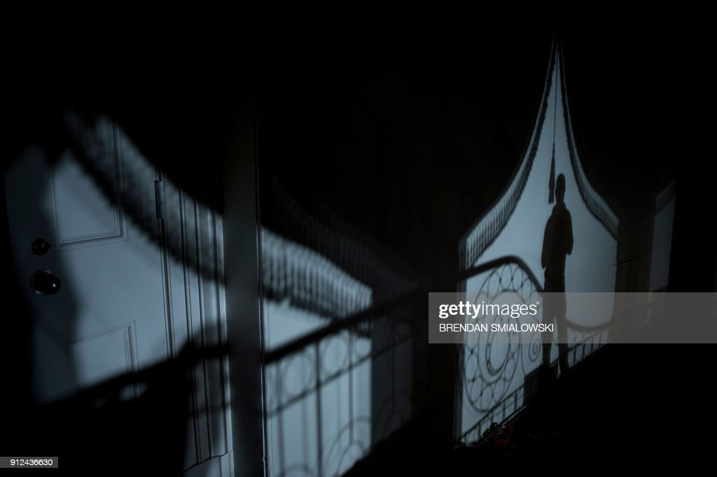 TOPSHOT - A shadow of a man is seen as he watches people make their way to interviews in Statuary Hall after the State of the Union address on Capitol Hill January 30, 2018 in Washington, DC. / AFP PHOTO / Brendan Smialowski