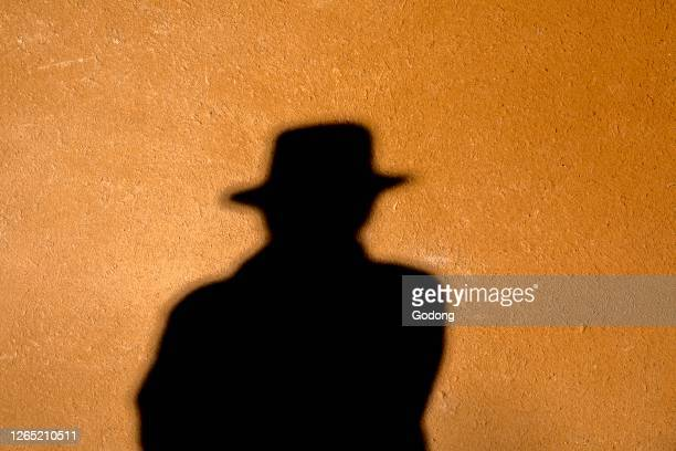 Shadow of a man wearing a hat on a wall. France.