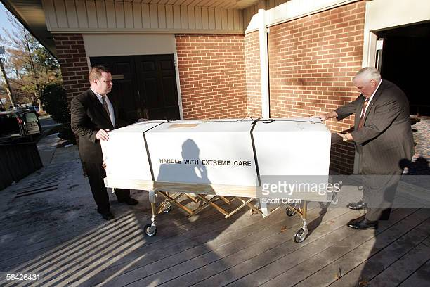 A shadow of a Marine escort is cast onto the packaging as funeral director apprentice Chris Moore and funeral director Bob Petty wheel the remains of...
