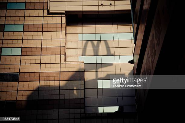 A shadow of a Mcdonald's restaurant sign projected over a facade of a skyscraper in Taipei