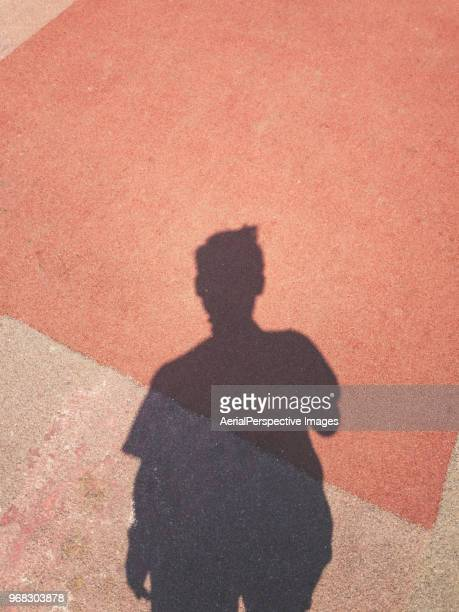 shadow of a men on street background using mobile phone - schaduw stockfoto's en -beelden