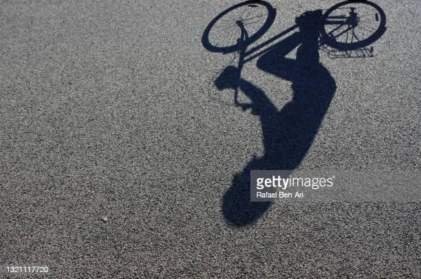 shadow of a person riding on a bicycle - rafael ben ari stock-fotos und bilder