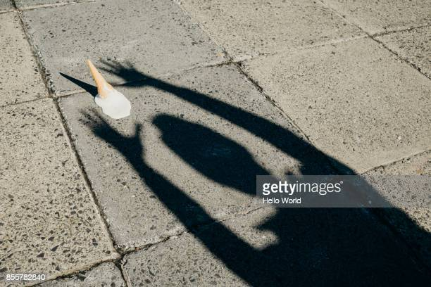 Shadow of a person's arms reaching for a fallen ice-cream cone