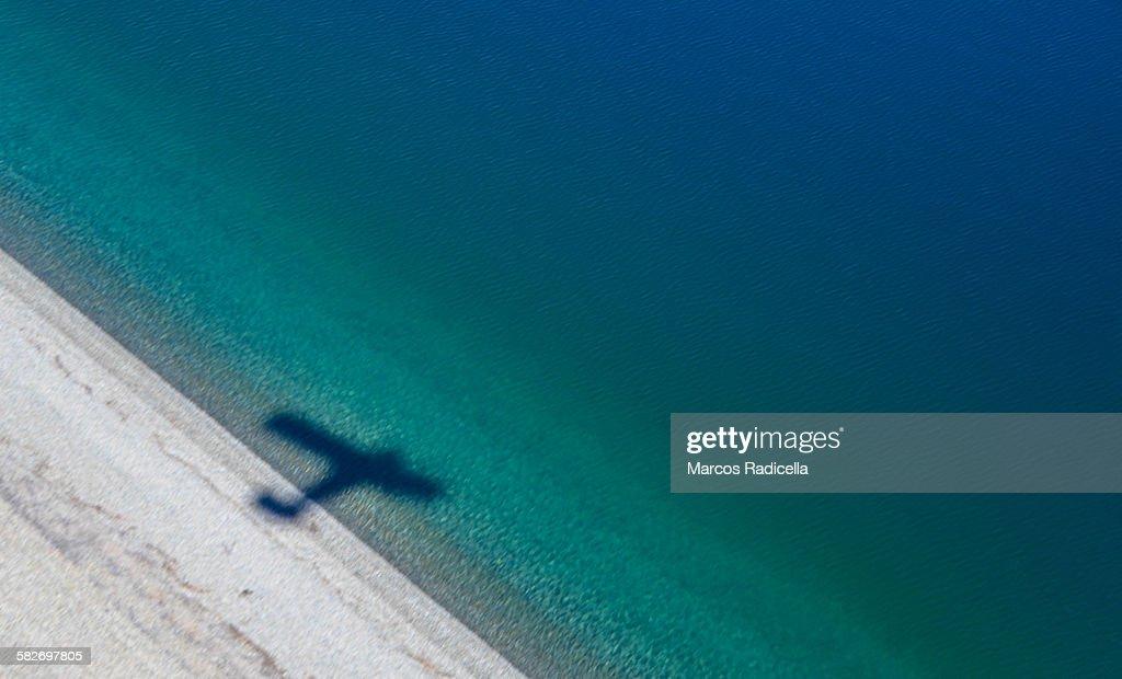 Shadow of a plane over lake coast : Stock Photo