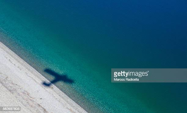 shadow of a plane over lake coast - radicella stock pictures, royalty-free photos & images