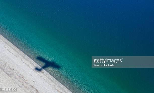 shadow of a plane over lake coast - radicella stockfoto's en -beelden